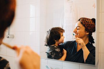 Mother carrying son while brushing teeth in front of mirror at home
