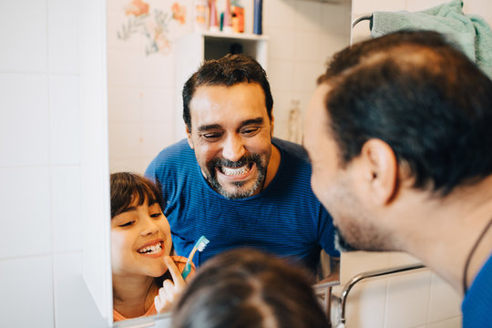 Father and daughter looking at teeth in mirror while brushing in bathroom