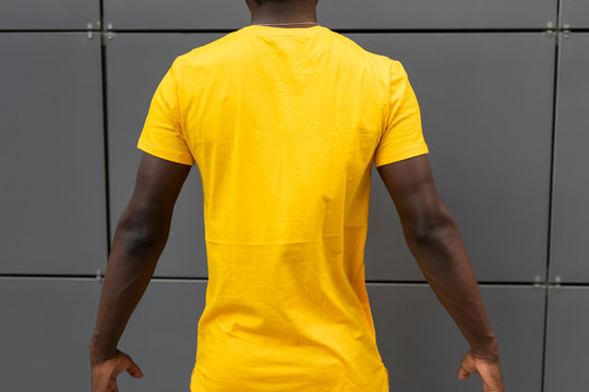 Empty blank yellow t-shirt on the american male back standing near wall, mockup design