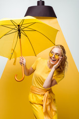 Obraz cheerful blonde girl looking at umbrella while touching sunglasses on white and yellow - fototapety do salonu