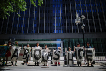 People pose for a picture in front of ICE's offices at the federal building during a protest against family deportations in the Manhattan borough of New York