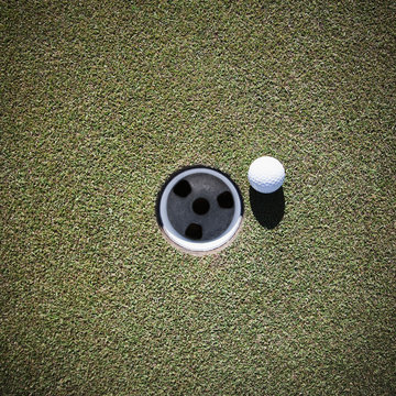 Golf Ball Next to a Putting Cup