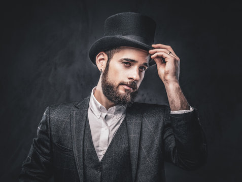 Portrait of a stylish bearded male in an elegant suit and cylinder hat, over dark background.