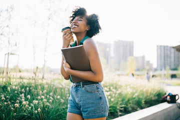 Emotional happy African American student with textbook in hands laughing feeling carefree, dark skinned excited woman with coffee to go enjoying recreation time in park during sunny summer day