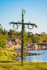 Sunrise of a classic midsommer pole at the coast line of Roslagen