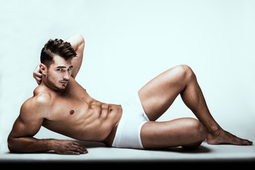 Portrait of handsome young man with stylish haircut in white underwear posing over white background. Perfect hair & skin. Close up. Studio shot