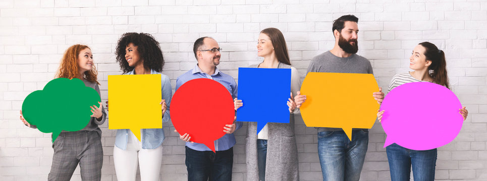 Cheerful diverse people holding empty colorful speech bubbles