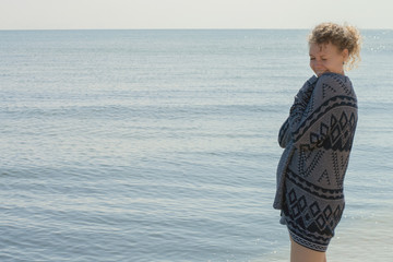 Pregnant smiling woman wrapped in knitted sweater at sea, copy space