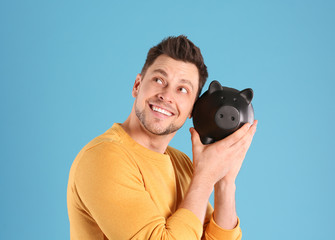 Man with piggy bank on color background