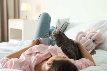 Young woman with cute cat on bed at home. Pet and owner