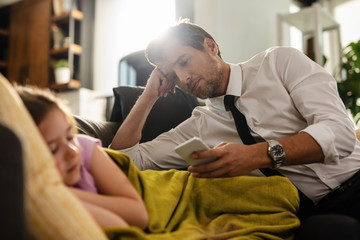 Businessman text messaging on cell phone while his daughter is sleeping next to his on the sofa.
