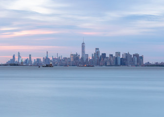 View on Financial District statue of liberty and jersey city from Hudson river at sunset with long exposure