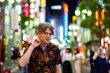 A man has an expression of not being able to hear well, while exploring the loud, vibrant city of Tokyo, Japan at night.