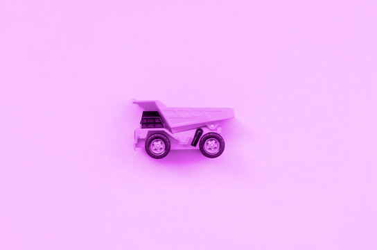 Small purple toy truck on texture background of fashion pastel purple color paper