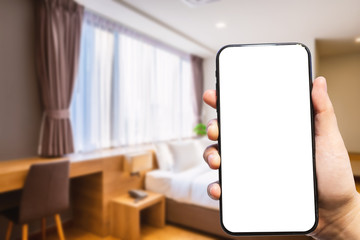 Close-up of female use Hand holding smartphone blurred images of defocused white pillow on bed decoration with light lamp in hotel bedroom interior background,Leisure and travel in the holiday concept