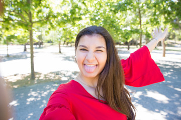 Playful young woman grimacing and taking selfie photo in park. Beautiful lady wearing red blouse, showing tongue and posing at camera with green trees in background. Selfie photo concept. Front view.