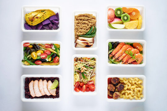 Weekly meal plan concept. Top view of various ready-to-eat dishes: seafood, meat, pasta, noodles, quinoa, veggies and fruits over white background.