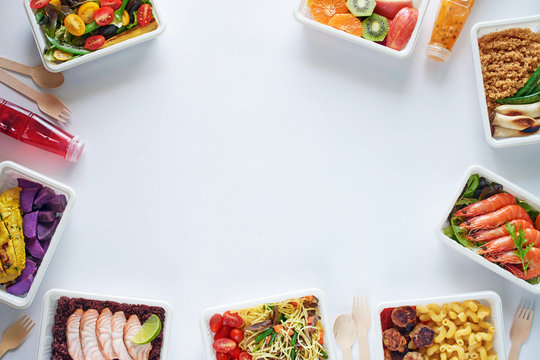 Prepared meal delivery concept with copy space. Top view of assorted ready-to-eat dishes over white background: seafood, meat, pasta, noodles, quinoa, veggies and fruits.