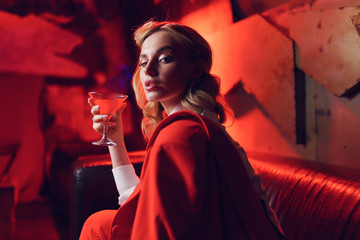 Photo of young blonde in red jacket with cocktail in her hand in nightclub