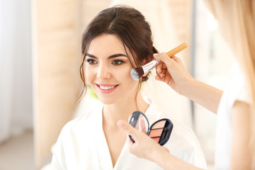 Professional makeup artist working with young bride at home Wall mural
