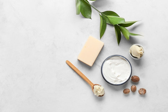 Shea butter with cream and soap on light background