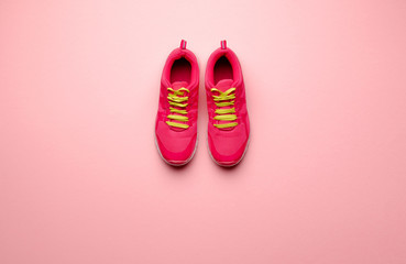 A studio shot of pair of running shoes on pink background. Flat lay.