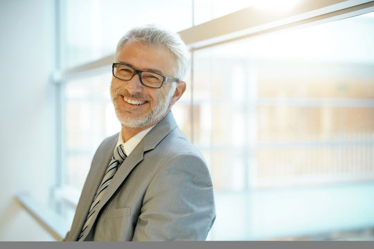 Smiling mature businessman leaning on office window smiling at camera