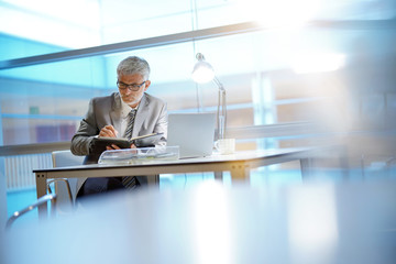 Mature businessman writing in agenda in modern office