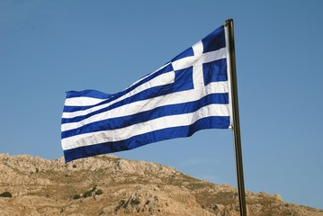 The Greek national flag flying on the seafront at Livadia on the Greek island of Tilos.