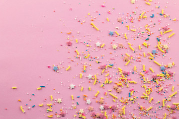 Sprinkles on pink background - Assorted colourful cake topping sprinkles scattered on pink on bottom corner with space for text - top view of star shapes, dots and oblong sprinkles