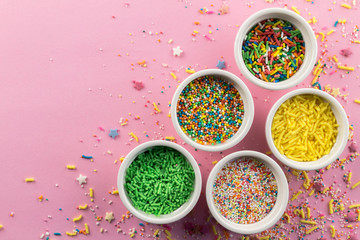 Cake sprinkles on pink background - Assorted colourful cake topping sprinkles in little white bowls on pink - top view