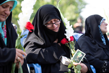 "Iranian women hold red flowers as they attend a ceremony to bury remains of 150 ""martyrs"" from 1980-88 Iran-Iraq war in Tehran"