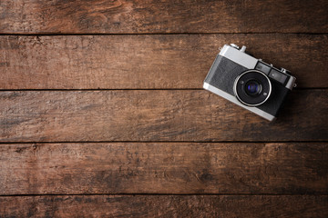 Old photo camera on wooden background