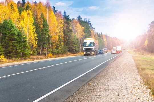 Trucks and cars go on the road in the autumn