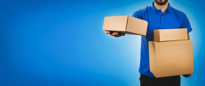 delivery service man holding cardboard boxes on blue background copy space