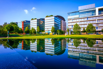 Urban landscape with modern office buildings, reflection on water surface of an artificial lake at summer and green park with grass and trees