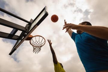 Players playing basketball at basketball court