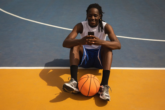 Basketball player using mobile phone while relaxing on basketball court