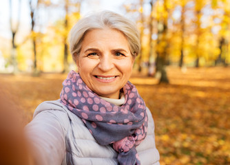 old age, retirement and technology concept - happy senior woman taking selfie at autumn park