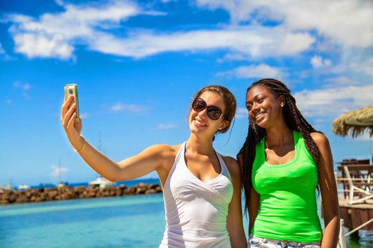 2 smiling girls taking a selfie against blue sky background.