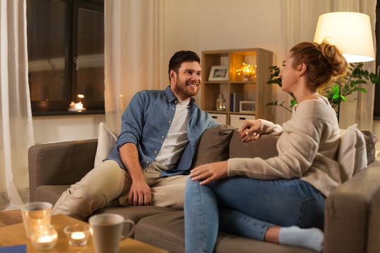 leisure and people concept - happy couple talking at home in evening