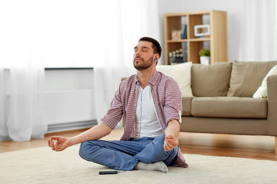 mindfulness, meditation and relaxation concept - man in earphones listening to relaxing music on smartphone and meditating in lotus pose at home