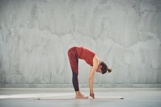 Side view of beautiful Caucasian brunette in red sports wear standing barefoot on the mat in Standing Forward Bend yoga posture.