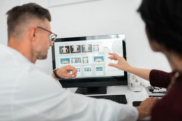 Plastic surgeon wearing glasses consulting client near computer