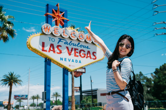 Happy young girl backpacker in sunglasses showing peace gesture and looking at camera while standing by famous billboard in nevada. smiling lady traveler taking picture with las vegas sign on summer