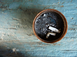 Two wasted cigarettes in a rusty ashtray on scratched wood, close up