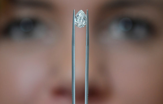 Sophie Lomax, Head of Design, holds a pear shape diamond at 77 Diamonds in London