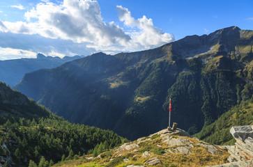 Ticino mountains and  a swiss flag near a mountain hut. Switzerland.