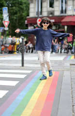 Playful child with sunglasses balancing arms in walking fun crosswalk