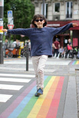 Happy child walking along the gay rainbow lines, cafe background